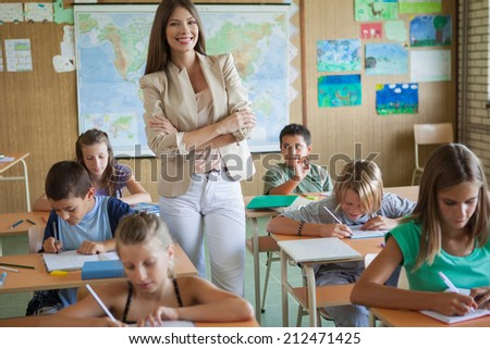 Smiling teacher with her students. - stock photo