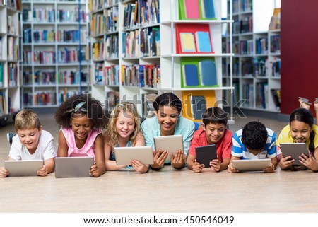 Smiling teacher with students using digital tablet while lying down in library - stock photo