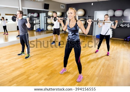 Smiling team doing squat exercises with weights at fitness gym - stock photo