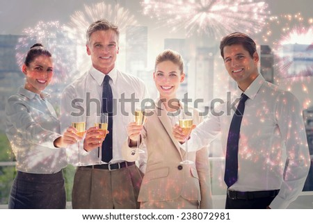 Smiling team of business people honoring a success with champagne against colourful fireworks exploding on black background