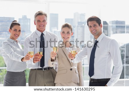 Smiling team of business people honoring a success with champagne in the office