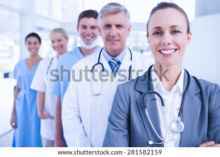 Smiling team of doctors standing in line in medical office - stock photo