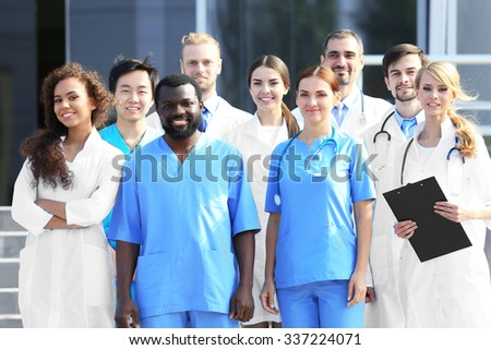 Smiling team of young doctors against hospital entrance - stock photo
