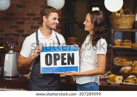 Smiling team posing with open sign at the coffee shop - stock photo