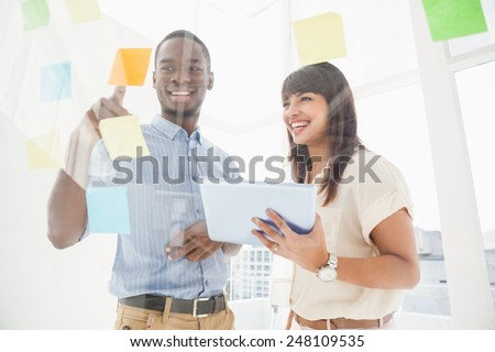 Smiling teamwork reading sticky notes and using tablet in the office - stock photo
