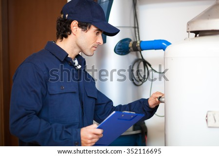 Smiling technician repairing an hot-water heater  - stock photo