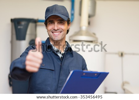 Smiling technician servicing a hot-water heater - stock photo