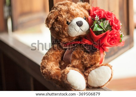Smiling teddy bear holding beautiful red roses bouquet. - stock photo