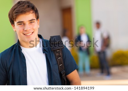 smiling teen boy carrying schoolbag - stock photo