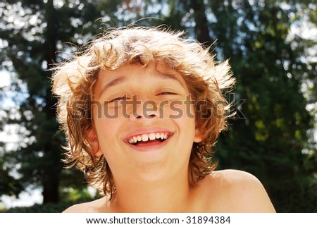 Smiling teen boy enjoying summer against blurry tree and sky background. - stock photo