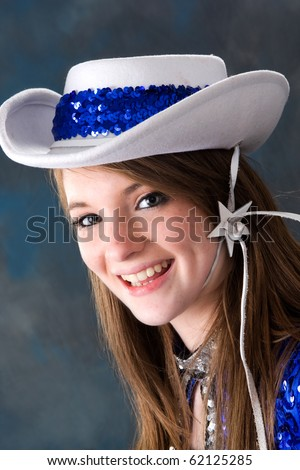 Smiling teen cheerleader wearing white and blue hat. - stock photo