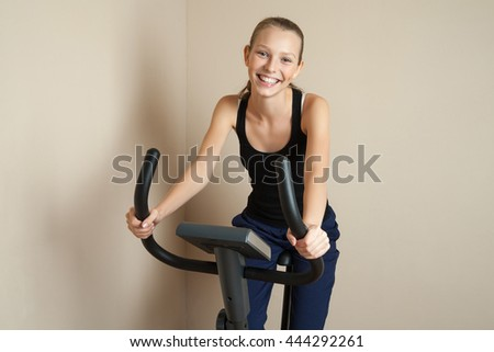 Smiling teen girl cycling at home - stock photo