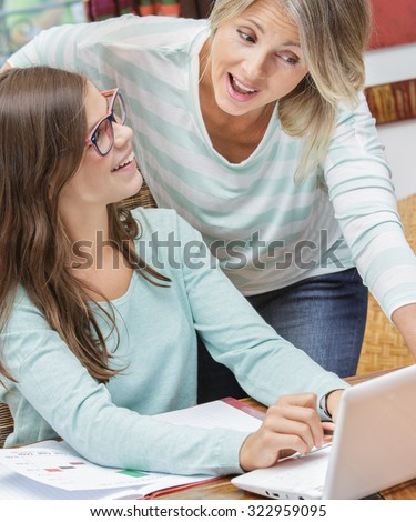 smiling teen girl doing homework with a blond teacher