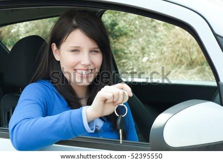 Smiling teen girl sitting in her car holding keys after bying a new car - stock photo