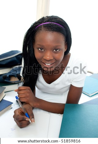 Smiling teen girl studying lying on her bed at home - stock photo