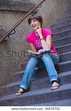 smiling teen girl with book on the stairs - stock photo
