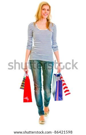 Smiling teen girl with shopping bags making step isolated on white - stock photo