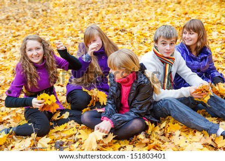 Smiling teen group sitting on yellow leaves - stock photo