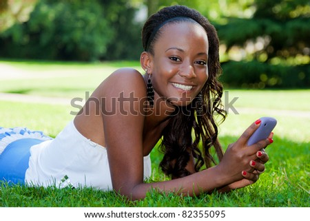 Smiling teenage black girl using a phone, lying on the grass - stock photo