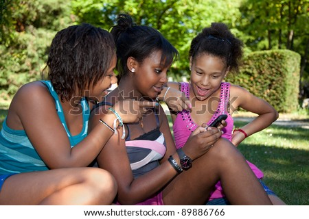 Smiling teenage black girls using a mobile phone at park - stock photo