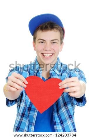 Smiling teenage boy holding valentine heart cut out from red paper with scissors over white background