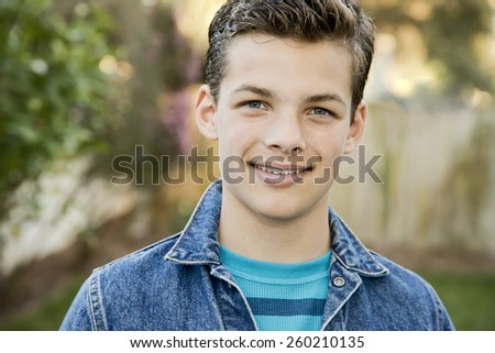 Smiling teenage boy outside, wearing denim jacket, horizontal format, 13 yrs old - stock photo