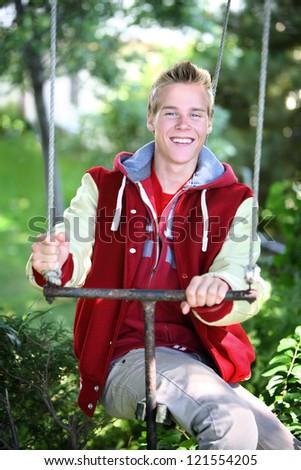 Smiling Teenage Boy sitting on a swing - stock photo