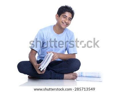 Smiling teenage boy sitting on floor with books against white background - stock photo