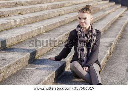 Smiling Teenage Caucasian Girl on Stairs. Horizontal Image Orientation - stock photo