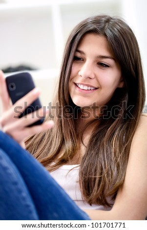 Smiling teenage girl checks her text messages on her mobile phone.
