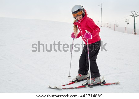 Smiling teenage girl equipped for skiing on snowy slope at ski resort. - stock photo