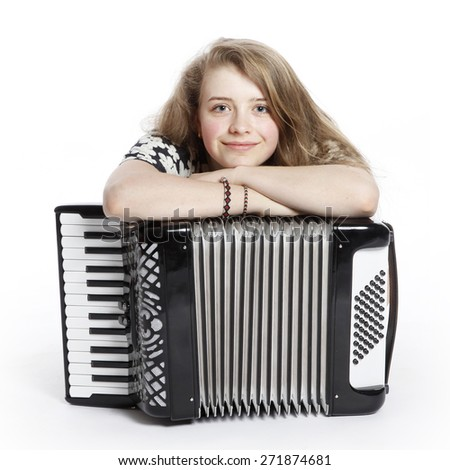 smiling teenage girl on the floor of studio with accordion against white background