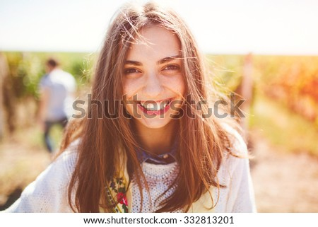 Smiling teenage girl outdoors on sunny day. Closeup of cute brunette young woman wearing casual clothes. - stock photo