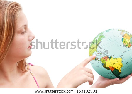 Smiling teenage girl points a finger on globe