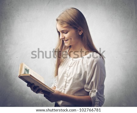 Smiling teenage girl reading a book - stock photo