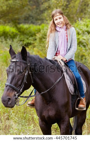 Smiling teenage girl sits on chestnut horse in the park. - stock photo
