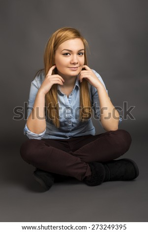 Smiling teenage girl sitting on the floor with legs crossed against gray background - stock photo