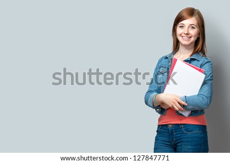 smiling teenage girl standing with books against the wall - stock photo