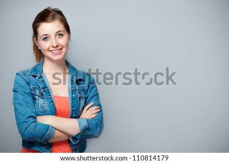 smiling teenage girl standing with crossed arms - stock photo