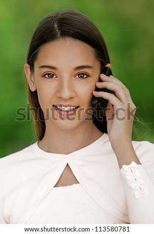 Smiling teenage girl talking on cell phone, against green of summer park. - stock photo