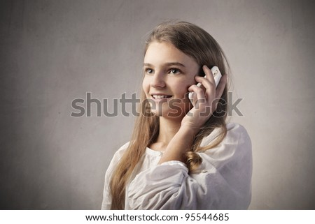 Smiling teenage girl talking on the mobile phone - stock photo