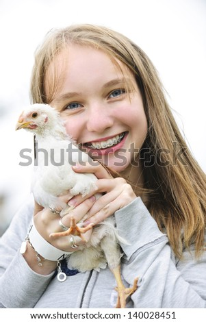 Smiling teenage girl with braces holding young chicken - stock photo