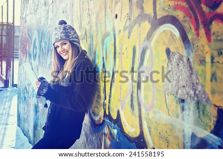 Smiling teenage girl with digital tablet outdoors in winter against graffiti wall. Cute blonde young woman with knitted hat smiling holding tablet. Horizontal, color filter, matte contemporary look. - stock photo