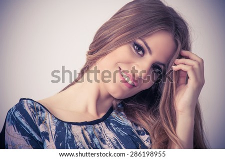 Smiling teenage girl with hand in her hair - stock photo