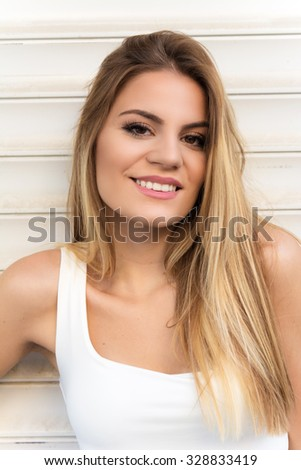 Smiling teenage girl with long straight hair posing - stock photo