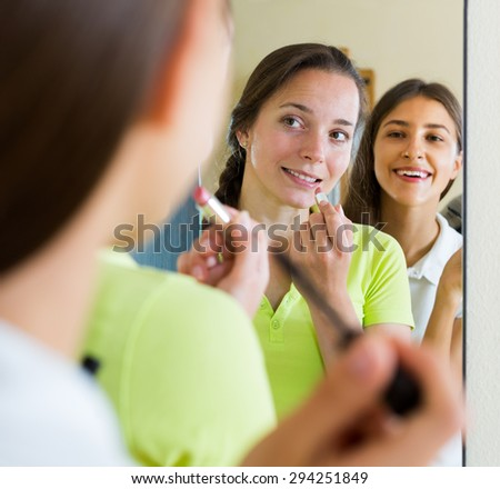 Smiling teenage girlfriends having fun while putting make up in front of the mirror