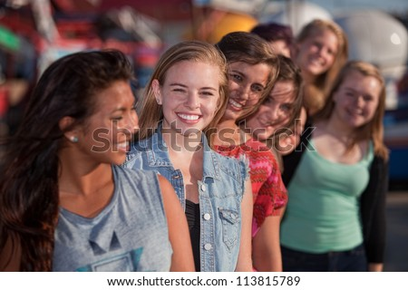 Smiling teenage girls standing behind each other in line - stock photo
