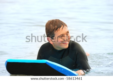 Smiling teenage surfer in a wetsuit laying on his bodyboard in the ocean.