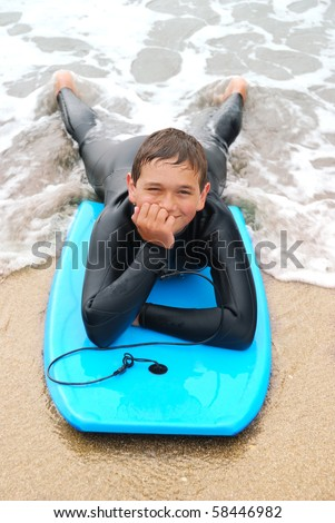 Smiling teenage surfer in a wetsuit laying on his bodyboard on the beach.