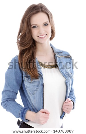 Smiling teenage woman in a trendy denim jacket looking at the camera, upper body studio portrait on white